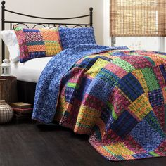This lovely quilt features patterned panels bursting with color along with a deep blue reverse. Matching shams are included to help decorate the bedroom.