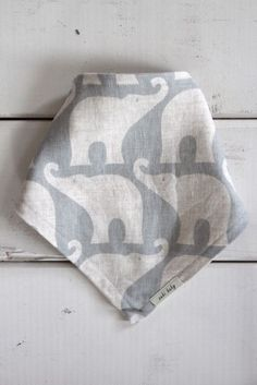 Baby bib by Zebi features pale blue elephants on parade.