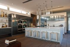 Seen in daylight, the kitchen holds the white and grey cabinetry over rich dark stained hardwood flooring, with natural light cascading through upper wall windows at left.
