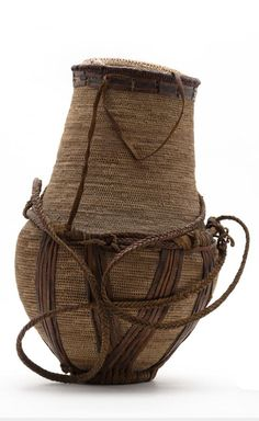 Water container made from coiled grass. The container is suspended in leather straps. There is a lid attached, made from a pale coiled grass...