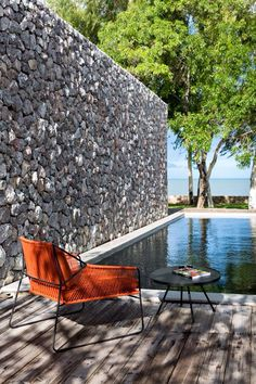 Outdoor design: orange outdoor lounge chair, stone wall, pool (mw)