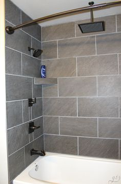 DIY How to Tile a Shower Surround with Tub | This master suite bathroom is spacious and luxurious. These grey ceramic tile ideas and designs are simple and beautiful for a remodel or new home build. This tutorial to install your own large tile on a budget will make you feel like a professional! Plus, we show you how to make gray shelves to hold your items and enjoy that rainfall shower head. Ooohh laaa laaa! #farmhouse #tile #rustic