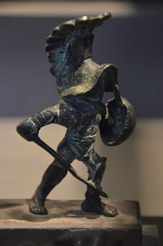 """A Hoplomachus (pl. hoplomachi) (Greek: ὁπλομάχος) (hoplon meaning """"shield"""" in Greek) was a type of gladiator in ancient Rome, armed to resemble a Greek hoplite (soldier with heavy armor and helmet, a round shield, a spear and a sword). The hoplomachus would wear a bronze helmet, a manica on his right arm, loincloth (subligaculum), heavy padding on his legs, and a pair of high greaves reaching to mid-thigh. His weapons were the spear and a short sword."""