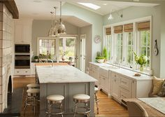 The cabinets are by Greenfield Custom Cabinetry. Door style is Augusta and the outer cabinets are Glacier White color. The kitchen island paint color is Eucalyptus.  The barn sconce over the kitchen sink is from Barn Light Electric.  Island pendant lighting are Benson Pendants in Polished Nickel from Restoration Hardware.  The counter stools are from William Sonoma Home. They are the 24″ diner stool in cream.  Kitchen ovens are by Wolf.