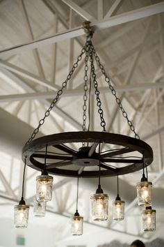 Wedding reception lighting idea - wagon wheel chandelier with hanging mason jars {EME Photography}