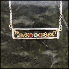 Sterling Silver frame with 18K Yellow Gold details, set with your choice of 1 to 4 synthetic birthstones.