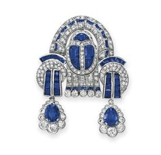 AN ART DECO DIAMOND AND SAPPHIRE BROOCH   Designed as a variously-cut diamond and sapphire sculpted plaque of geometric motif, suspending two pear-shaped sapphire and circular-cut diamond pendants, mounted in platinum, circa 1925, with pendant hook for suspension