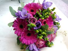 A vibrant brides maid bouquet, flowers used: cerise germini, lilac freesia, lilac roses, green hypericum berries and eucalyptus.