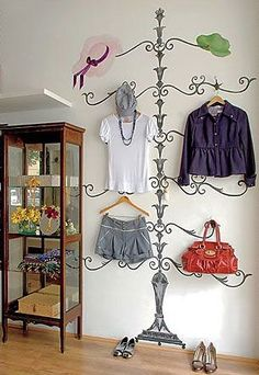 Decal on wall with clothing items placed strategically on hooks.