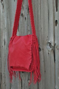 A crossbody handbag made of soft red leather. This bag is 12 inches tall, 11…