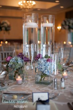 Flowers in bottom of glass cylinder with floating candle at top.   KJwedLG-1033