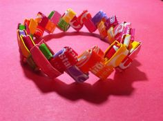 DIY How To Make A Bracelet Out Of Candy Wrappers!  Do you remember making these when we were kid out of gum wrappers?! I forgot how to make them so I'm tickled pink to see this!