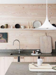 Теплые оттенки и текстуры дерева в отделке кухни оттеняются серым бетоном кухонных столешниц. .