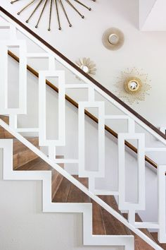 CUSTOM STAIR RAILING BY BECCA STEPHENS INTERIORS; BRASS STARBURST/SUNBURST MIRRORS; MOD RECTANGULAR CUT-OUTS; FAUX WOOD CERAMIC TILE; WALNUT HANDRAIL. BOHO LUXE DECOR; BOHEMIAN MID-CENTURY DESIGN. PHOTO BY MOLLY WINTERS PHOTOGRAPHY