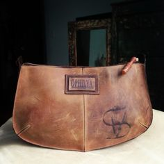 Ophilya handmade leather clutch with wooden lathe zipper pull.