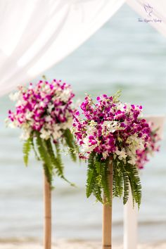 Local pink and white orchids drape over the greenery and natural bamboo stands for this aisle decoration