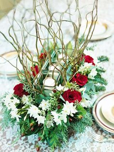 Three glass votive cups held by twigs on a block of soaked florist's foam with flowers & greens arranged around sides, draping down to tabletop
