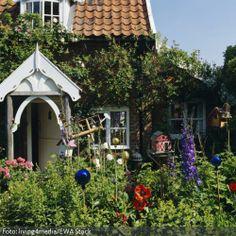 Ein wenig märchenhaft wirkt der Eingangsbereich von dem Friesenhaus mit dem Blumenbeet im Vorgarten. Der urige Eindruck entsteht durch das weiße Spitzdach über dem Eingangsbereich und den hohen farbigen Blumen, die den Vorgarten schon fast etwas wild erscheinen lassen.