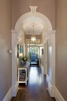 European oak floors, plantation shutters and ornate ceilings highlight the designer's attention to detail through this double arched hallway