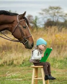 Horse standing behind watching a little girl read a book while sitting on a stool. Curious horse, good friend. Cute!