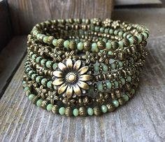 This 7 coil bracelet is made with brass memory wire - will adjust to the size of your wrist and no chance of breaking. This will ensure you will have this bracelet for a long time. Materials include 4mm faceted green glass and an assortment of brass spacer beads, including tiny flower
