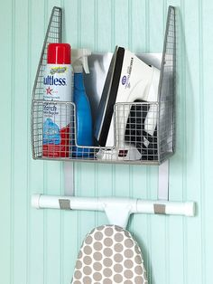 LAUNDRY/IRON: Save Floor Space A metal mesh caddy secures the ironing board to the wall when not in use, and its built-in basket provides handy storage for the iron and spray starch.