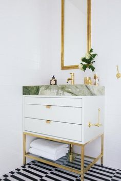 Stunning bathroom features a white lacquer dresser like vanity with glass shelf topped with gray stone fitted with a brass faucet and a brass toilet paper roll holder and an antique brass framed medicine cabinet alongside a black and white striped tile floor.