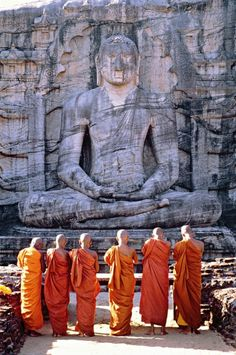 beautiful photo of monks praying in front of Buddah carved out in a side of a mountain.