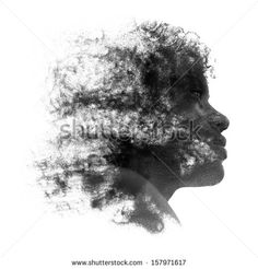 Artistic portrait of a young African woman with fine grains of sand caught in her curly frizzy hair and coating the skin of her face, black and white profile image isolated on white