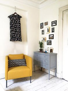 Beautiful old apartment with some stucco, a yellow armchair and and old vintage cupboard. We love this gallery wall! Check out our website to find more of our interior designs!