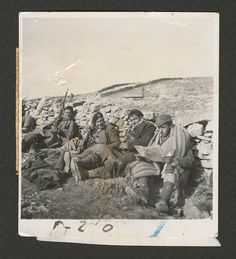 Spain - 1938. - GC - After Teruel [4 soldiers sitting against wall, one reading a newspaper]