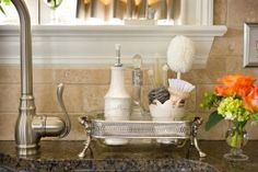 Here's another fun idea: Find an attractive tray and fill it with all your sink-side essentials, like dish soap, hand soap, hand lotion and scrubbers. Suddenly, that unattractive stuff becomes a design feature.