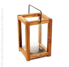 Only the golden tone of teak can give these lanterns their simple, rich look. Our tree-farmed teak harms no natural forests. Clever carpentry conceals that one panel of the lantern slides open for easy lighting and cleaning. A sturdy handle allows for easy placement on the patio or in the home.