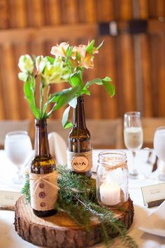wooden slab centerpiece with bottles used as vases for table decoration Wooden Slab Centerpiece, Wooden Slab Table, Unique Wedding Cakes, Rustic Wedding, Beer Bottle Centerpieces, Wedding Table Toppers, Deco Champetre, Marriage Reception, Low Budget Wedding