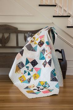 This is a happy quilt! Make it using two time-saving techniques — Quick Triangle-Squares and Quick-Pieced Flying Geese Units and beautiful patterned fabrics.