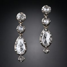 his shimmering pair of diamond drop earrings, crafted in silver over gold, date back to the early-to-mid 1800s - the pre-Victorian or Georgian jewelry period. A pair of pear-shape rose-cut diamonds, punctuated with a tiny rose-cut diamond below, dance below a couple of small, roundish, rose-cut diamonds, which together measure just shy of one inch in length. A very beautiful and subdued pair of original antique diamond earrings.