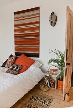 Bedroom - wood floors, white bedspread, color pops on wall and floor