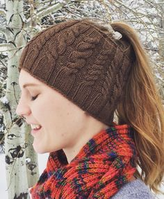 Free Knitting Pattern for Yellowstone Skate Ski Hat - Cabled ponytail / messy bun hat that can also be worn as a neckwarmer cowl. Designed by Selena Miskin