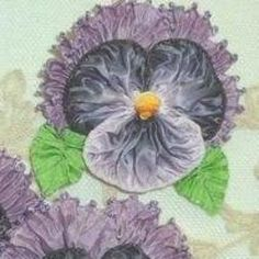 French picot and ombre ribbon flower pansy is made using ribbons that have been softly ruched. Pansy features vintage ribbon leaves, a knotted ombre ribbon center and is 2 inches in diameter.