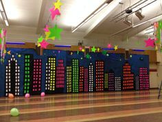 GLOW IN THE DARK school dance...(before black lights are activated).  City scene painted on thick plastic, neon cutouts form windows.  Neon stars cut out of posterboard are hung from wires and everything glows under the black light, even the black light activated balloons.
