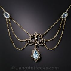 Antique Aquamarine Necklace.  Antique swag necklace, dating from the turn-of-the-century, highlighting three pretty, pastel blue aquamarines: a pear shape center and a pair of matching ovals.