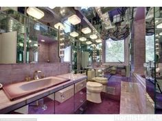Unique bathroom features: One home owner has stamped their own individual mark on this bedroom, which is decked out with wall and ceiling mirrors, a purple carpet, lilac tiles and gold-coloured taps