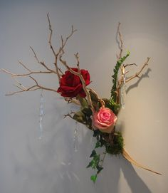 A manzanita branch with red and pink roses. See our entire selection at www.starflor.com.  To purchase any of our floral selections, as gifts or décor, please call us at 800.520.8999 or visit our e-commerce portal at www.Starbrightnyc.com. This composition of flowers is generally available for same day delivery in New York City (NYC). MA009