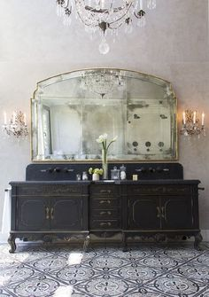 Antique cabinetry upcycled into a bathroom vanity unit paired with antique lighting fixtures and encaustic tiles