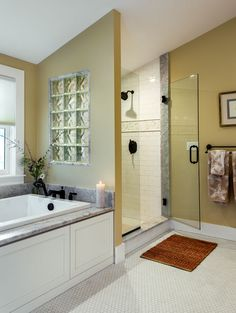 Maine oceanfront cottage master bathroom with soaking tub; shower with glass block tile; white mosaic floor tile