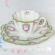 A very old English porcelain tea trio featuring unusual pattern of violet floral wreaths and ribbon bows, and pretty scallop shapes. This is likely a hard paste porcelain tea set made early 1900s, or earlier - late 1800s. An antique for the collector. Condition of the set: good,