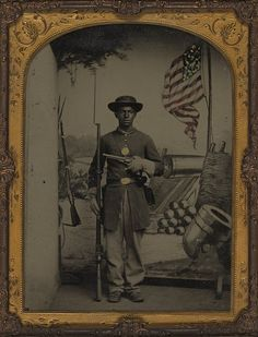 Unidentified African American soldier in Union uniform with a rifle  and revolver in front of painted backdrop showing weapons and American  flag. c. 1864
