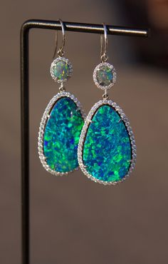 18K White Gold diamond encrusted earrings made with both solid black opal and australian opal doublets. 2 carats of diamonds. Hand made, one of a kind dangle earrings that will knock you out of your s #opalsaustralia