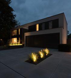 Moderne Architektur. Einfahrt mit Metten Betonsteinplatten von Rheingrün. Beleuchtet in der Dämmerung. Wohlfühlen zu hause.