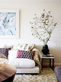 Neutral living room with small tree on side table, purple, patterned pillow on sofa, and blue art